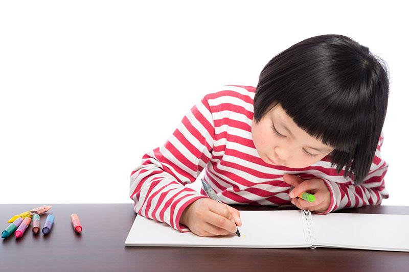 マンガを描いている小学生